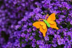 Felt butterfly atop a violette lilac bush Stock Images