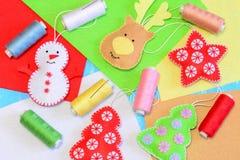 Felt Christmas ornaments. Colorful stuffed felt snowman, reindeer, Christmas tree, flat felt sheets, colored thread, needle Stock Photos