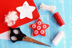 Felt Christmas star decor, paper pattern pinned to red felt sheet, scissors, thread, needle, cord on blue wooden background Stock Image