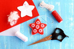 Felt Christmas star diy, paper pattern pinned to red felt sheet, scissors, thread, needle, cord on blue wooden background Stock Image