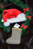 Felt christmas stocking, a christmas hat, a green garland Royalty Free Stock Photos