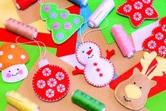 Felt Christmas tree ornaments. Funny felt snowman, deer, Christmas tree, ball, mushroom diy, polyester felt, thread, needle. Kids Christmas diy background Royalty Free Stock Photography