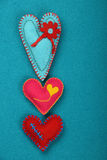 Felt craft and art three stitched hearts on blue Royalty Free Stock Image