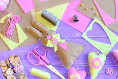 Felt Easter bunny with hearts. Easter wall decor idea. Scissors, pins, thread spools, thimble, buttons and beads in a box Stock Image