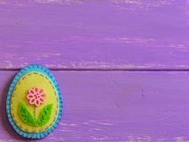 Felt Easter egg decor with pink flower  on a wooden background with copy space. Fun Easter crafts for kids. Happy Easter Royalty Free Stock Images