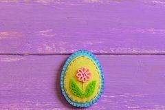 Felt Easter egg ornament with pink flower button  on a wooden background with copy space. Fun Easter sewing crafts Royalty Free Stock Photography