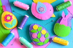 Felt Easter eggs with flowers and bunny, a bird. Easter DIY set, colored thread spools, felt sheets, pins on a table Stock Photography