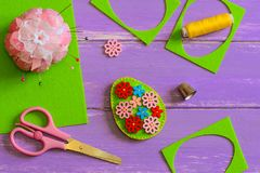 Simple felt Easter egg decoration idea. Hodemade felt Easter egg with colored wooden flower buttons. Felt scrap, scissors, thimble. Felt Easter pattern. Tutorial Stock Photos