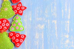 Felt green and red Christmas tree, ball, star ornaments on a blue wooden background with copy space for text on the right side Stock Images