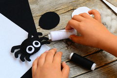 Felt Halloween spider ornament, thread, needle, paper templates, filler, white and black felt sheets on a vintage wooden table Royalty Free Stock Images