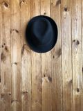 Felt hat on a wooden background. Black classic hat hanging on a wooden wall. Felt hat on a wooden background. Blogger attribute, fashion accessory Royalty Free Stock Photo