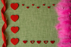 Felt heart and dyed bird feathers on fabric background Royalty Free Stock Photography