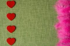 Felt heart and dyed bird feathers on fabric background Stock Photo