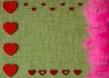 Felt heart and dyed bird feathers on fabric background Stock Image