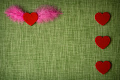 Felt heart and dyed bird feathers on fabric background. Valentine`s card stock photos