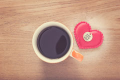 Felt heart with Made With Love button and cup of coffee on woode Stock Photo