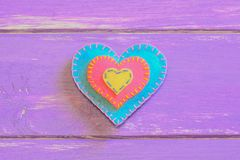 Felt heart  on a purple wooden background with copy space for text. Felt valentine. St. Valentines Day symbol. Top view Stock Photo