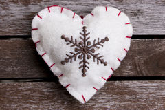 Felt heart. White felt heart with embroidery on wooden surface Royalty Free Stock Images