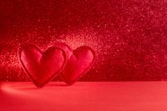 Felt hearts on red background with bokeh. Valentine`s day celebration or love concept. Copy space. Toned stock image