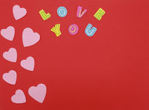 Felt hearts on red background with Love you text Stock Images