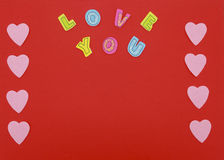 Felt hearts on red background with Love you text. Felt hearts and colorful letters on red background. Space in the center can be used for greeting text Stock Photography
