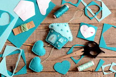 Felt house with hearts decoration, tools and materials for sewing, paper patterns on old wooden background. Hanging wall decor Royalty Free Stock Photo