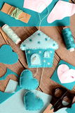 Felt house with hearts ornament, tools and materials for hand making felt crafts, paper patterns on wooden table Royalty Free Stock Photography