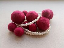 Felt jewelry balls pearl chain on light background royalty free stock photos
