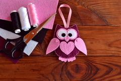 Felt owl embellishment. Felt owl toy. Kids DIY crafts. Sheets of colored felt, scissors, thread, needle, wooden table. Sewing crafts. Easy crafts from felt. Felt Royalty Free Stock Image
