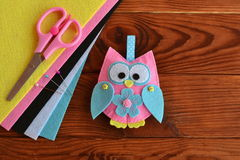 Felt owl embellishment. Felt owl toy. How To make a pretty felt owl - kids DIY crafts tutorial. Sheets of colored felt, scissors, wooden table Royalty Free Stock Image