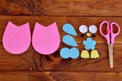 Felt owl patterns, scissors on a wooden table. How to make a cute felt owl embellishment. Kids needlecraft tutorial. Top view. Closeup Stock Photo