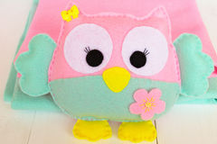 Felt owl on a white wooden background, rolls of pink and blue felt Stock Image
