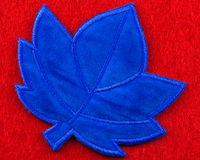 Felt patch. One blue stitched felt maple leaf shaped patch on a red background Stock Photos