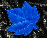 Felt patch. One blue stitched felt maple leaf shaped patch on a sparkly background Stock Images
