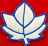 Felt patch. One blue and white stitched felt maple leaf shaped patch on a red background royalty free stock photos