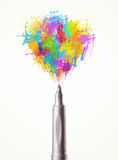 Felt pen close-up with colored paint splashes Royalty Free Stock Photography