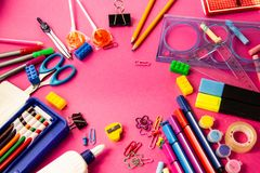 Felt pens, pencils, clips of different colors on a pink background royalty free stock photography