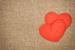 Felt red hearts on the burlap Royalty Free Stock Photo