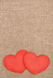 Felt red hearts on the burlap Stock Image