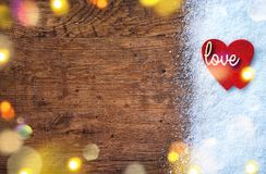 Felt red hearts and wooden inscription `love` on snow and rustic background. Love and St. Valentines Day concept Royalty Free Stock Photos