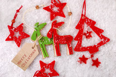 Felt reindeers and stars decorations on snow with paper tag Royalty Free Stock Image