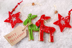Felt reindeers and stars decorations on snow with paper tag Stock Image