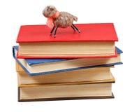 Felt soft toy lamb on stack of books. Isolated on white background stock image