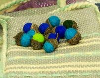Felt souvenir handmade acorns on the rug woven by hand. Traditional crafts of Bulgaria Stock Photos