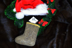 Felt stocking and a Christmas hat on the fir Stock Image