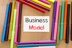 Felt-tip pen and note and business model text concept. Felt-tip pen and note on a wooden background and text concept Royalty Free Stock Image