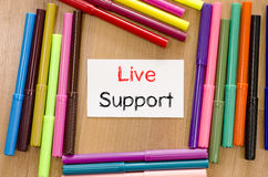Felt-tip pen and note and live support text concept. Felt-tip pen and note on a wooden background and text concept Stock Photo