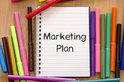 Felt-tip pen and notepad and marketing plan text concept. Felt-tip pen and notepad on a wooden background and text concept Royalty Free Stock Photo