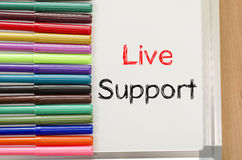 Felt-tip pen and whiteboard and live support text concept. Felt-tip pen and whiteboard on a wooden background and text concept Stock Photos