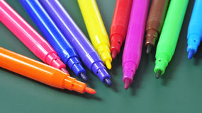 Felt-tip pens of different colors. A pile of felt-tip pens of different colors on a green chalkboard royalty free stock photo